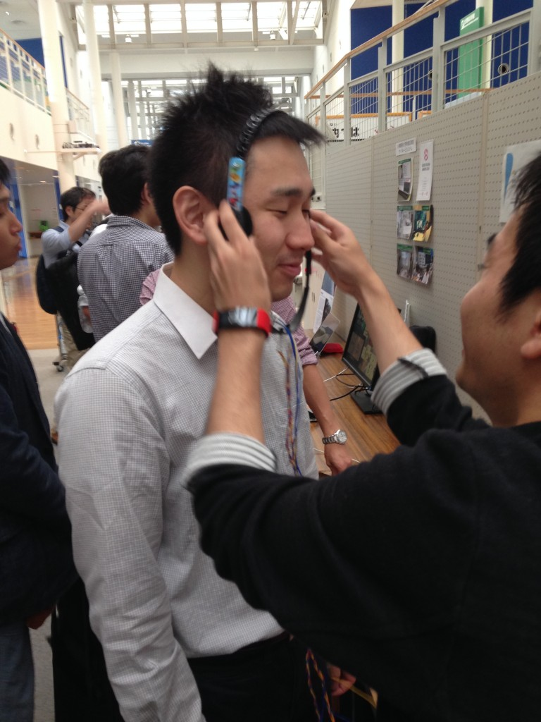 He is putting on a wearable system for monitoring a person chewing. Then, the system gives some haptic feedback to chew the food more, when he didn't chew enough.